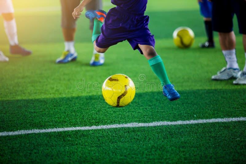 Boule de jaune de pousse de footballeur d'enfant sur le gazon artificiel vert image libre de droits