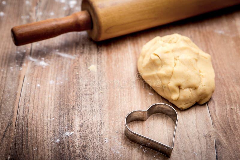 Boule de la pâte de biscuit, coupeur en forme de coeur et goupille sur en bois images libres de droits