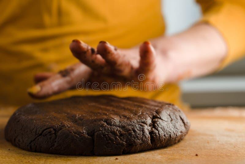 Boule de la pâte et du cacao pressés à un conseil en bois avec votre plan rapproché de mains image stock