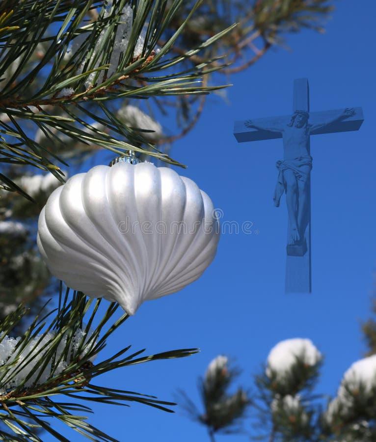 Boule de Noël blanc sur le vrai arbre de Noël extérieur vivant avec le crucifix semi-transparent photographie stock