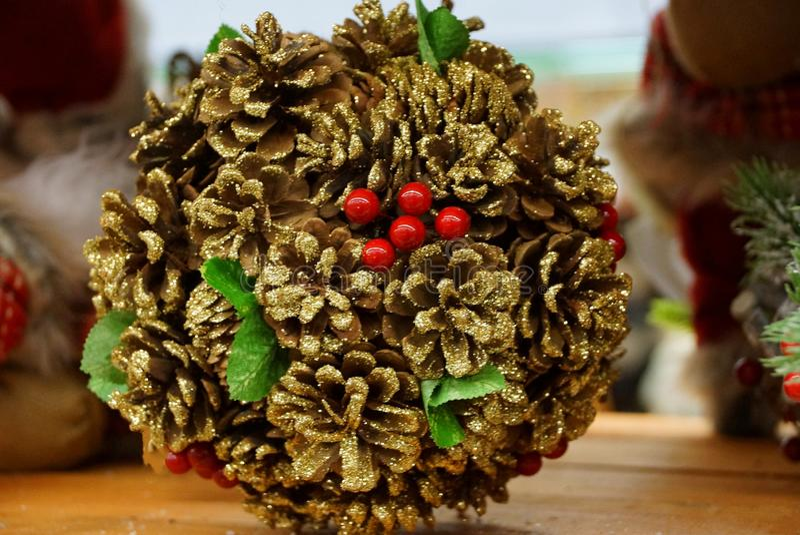 Boule de Noël des cônes bruns et des baies rouges sur la table photos stock