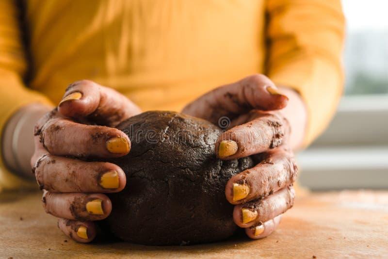 Boule de pâte et de cacao dans des mains sur un conseil en bois photos stock