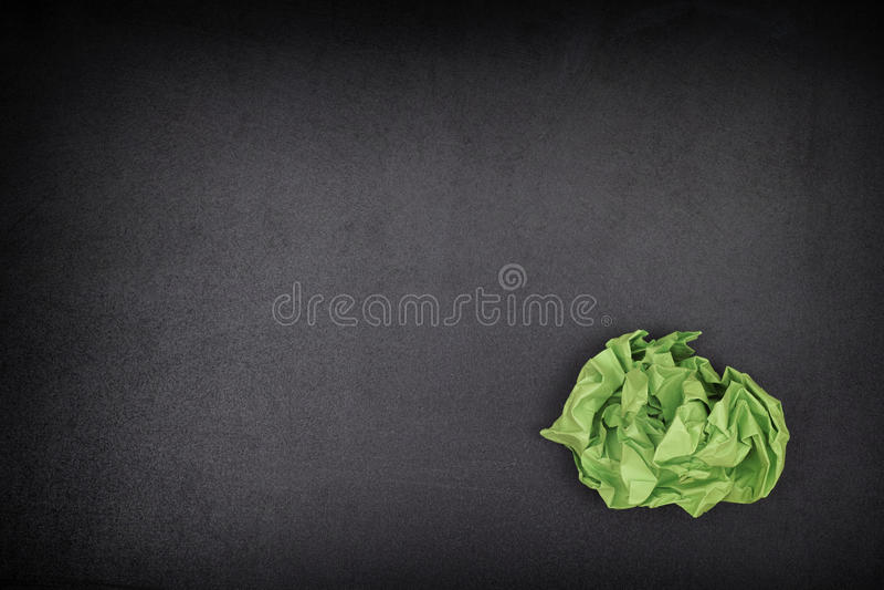 Boule de papier chiffonnée par vert sur un tableau noir photo libre de droits