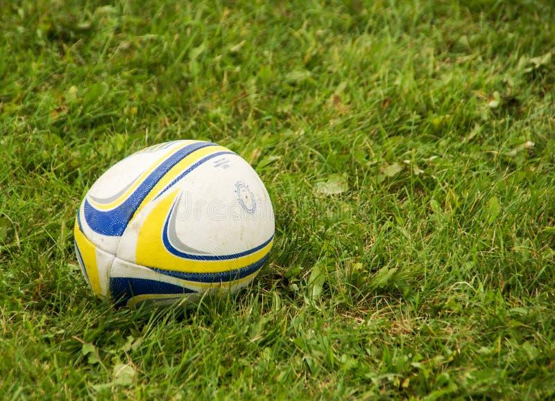 Boule de rugby bleue, jaune, et blanche se reposant dans l'herbe verte dans le Wisconsin supérieur images libres de droits