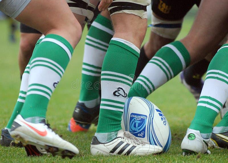 Boule de rugby entre les jambes de joueurs dans le jeu de généraliste du rugby 7's image libre de droits