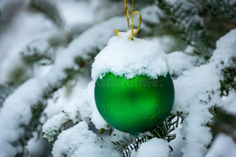 Boule de vert de jouet d'arbre de Noël accrochant sous la neige sur une branche de sapin du côté droit photographie stock