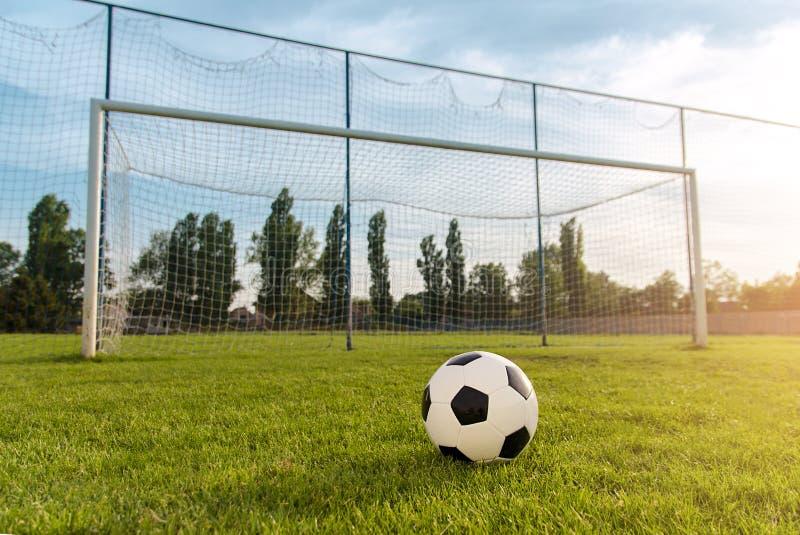 Boule du football/football devant le but vide au coucher du soleil photographie stock libre de droits