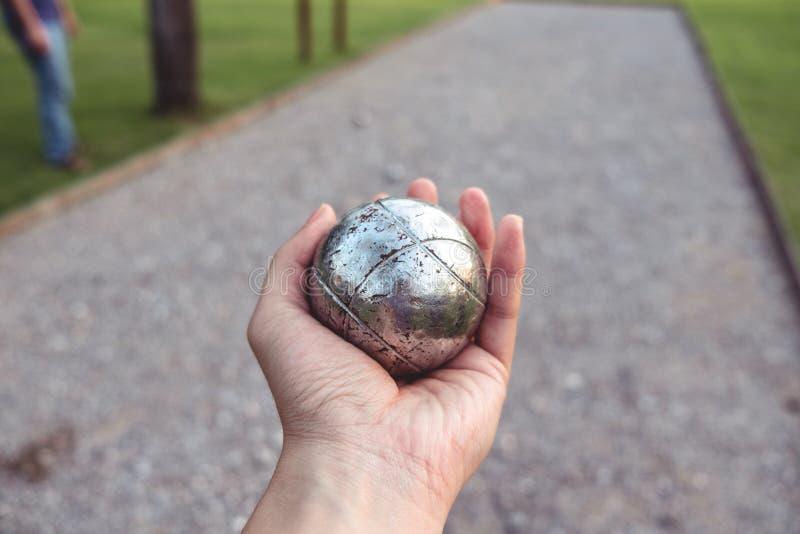 Boule en métal de Petanque en main images stock