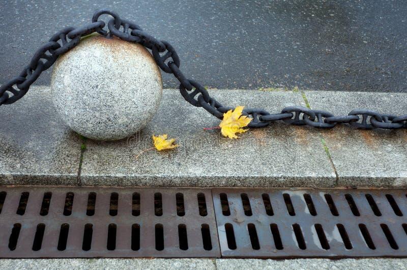 Boule en pierre avec une grande chaîne de metall, leav jaune d'érable de l'automne deux images libres de droits