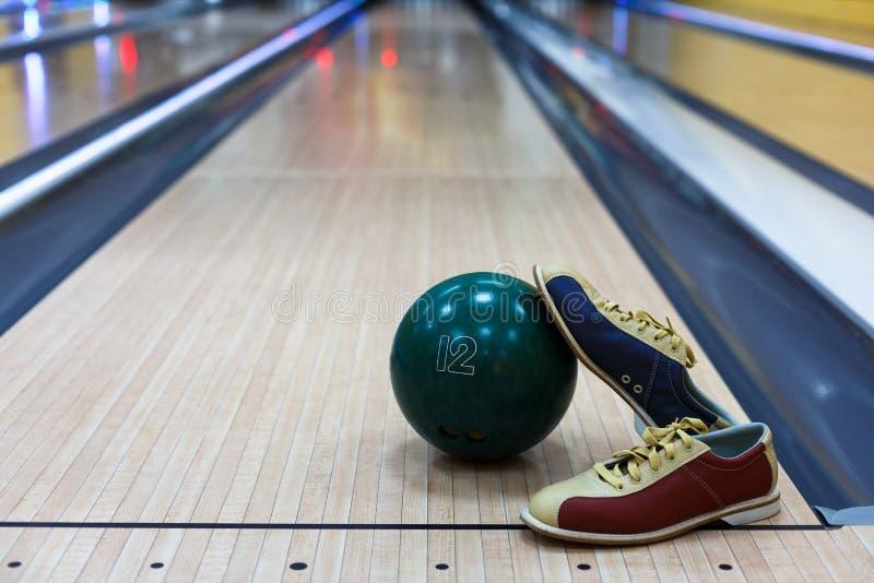 Boule et chaussures de bowling sur le fond de ruelle photo libre de droits