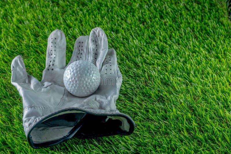 Boule et gant de golf sur l'herbe image libre de droits