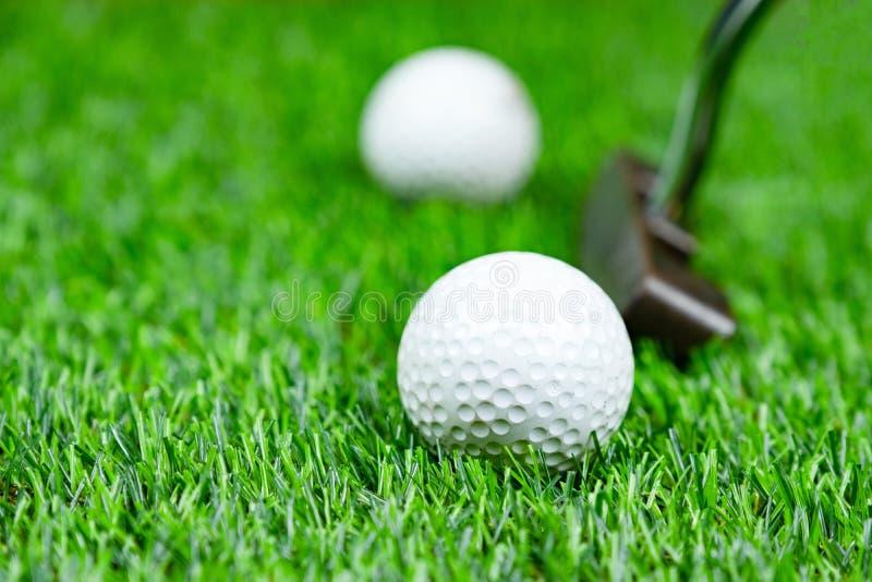 Boule et putter de golf sur l'herbe photos stock