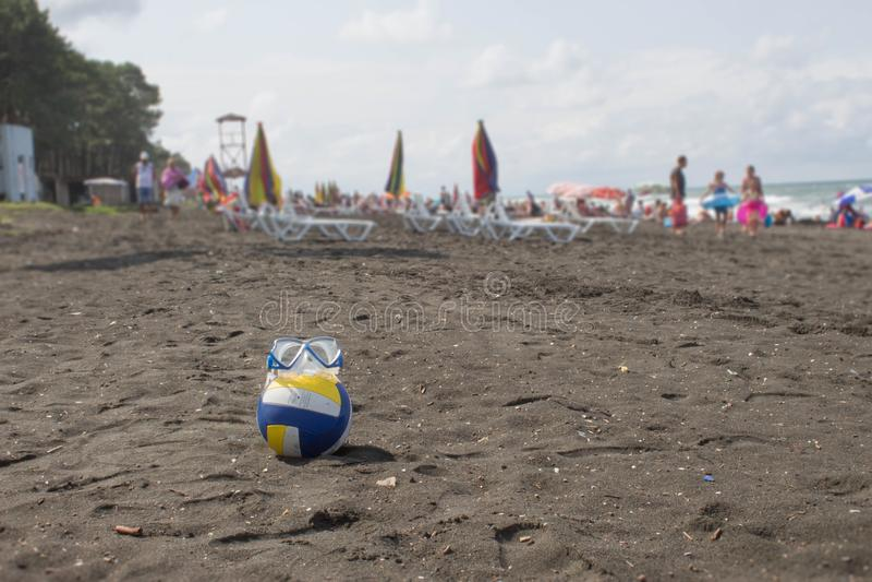 Boule et verres de natation sur la plage Photo brouillée des personnes sur la plage de sable Voyage ou concept de vacances de mer photos stock