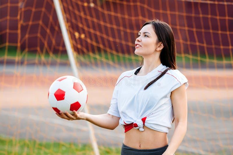 Boule femelle de gardien de but dans des ses mains, se tenant au but du football photographie stock