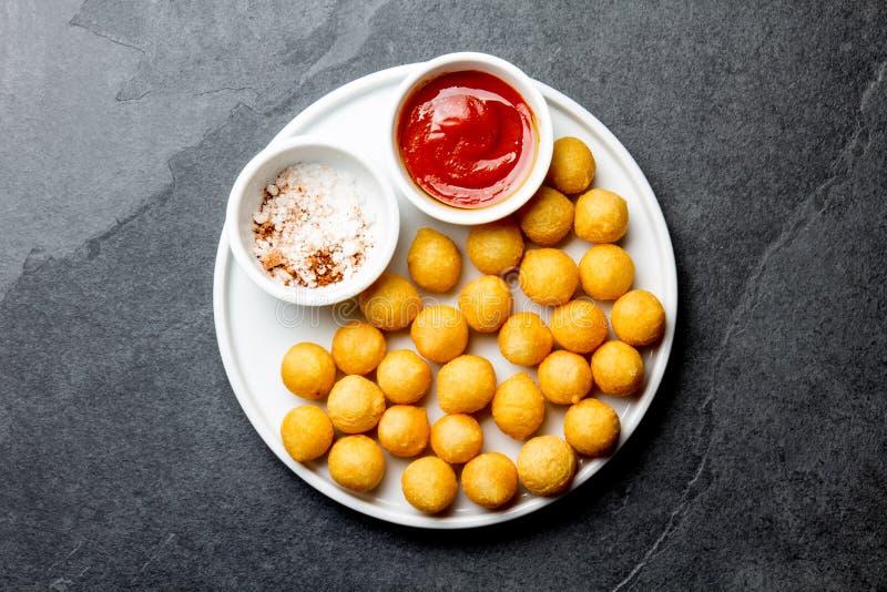 Boule frite de pommes de terre, crocettes du plat blanc avec la sauce tomate, fond d'ardoise, vue supérieure images stock
