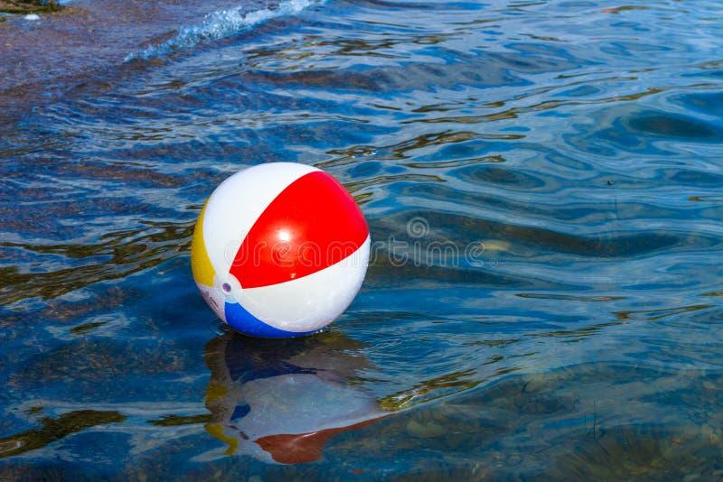 Boule gonflable de plage flottant dans l'eau photographie stock libre de droits