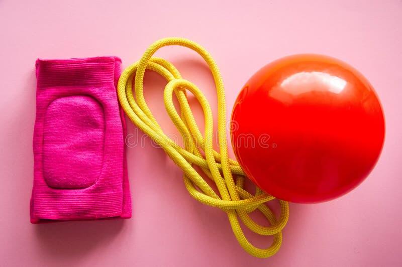 Boule gymnastique rouge, kneepads et corde à sauter sur un backgro rose photographie stock