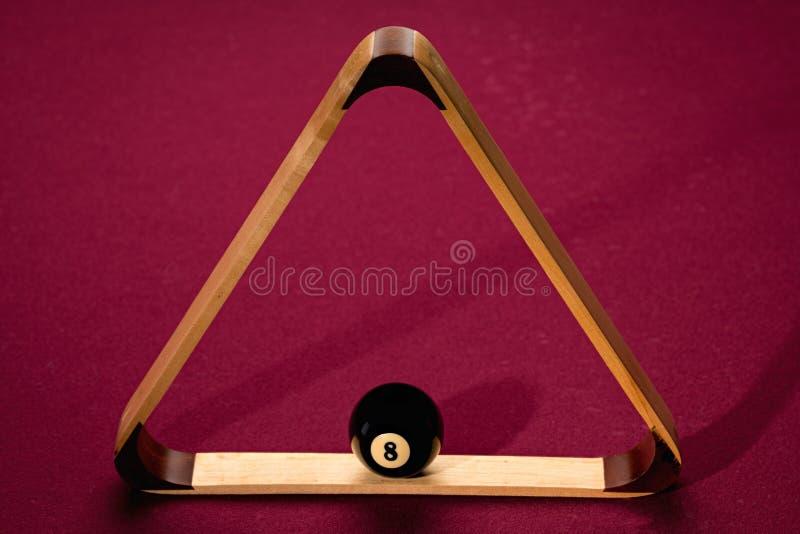 Boule huit placée dans un support de triangle sur une table de billard image stock