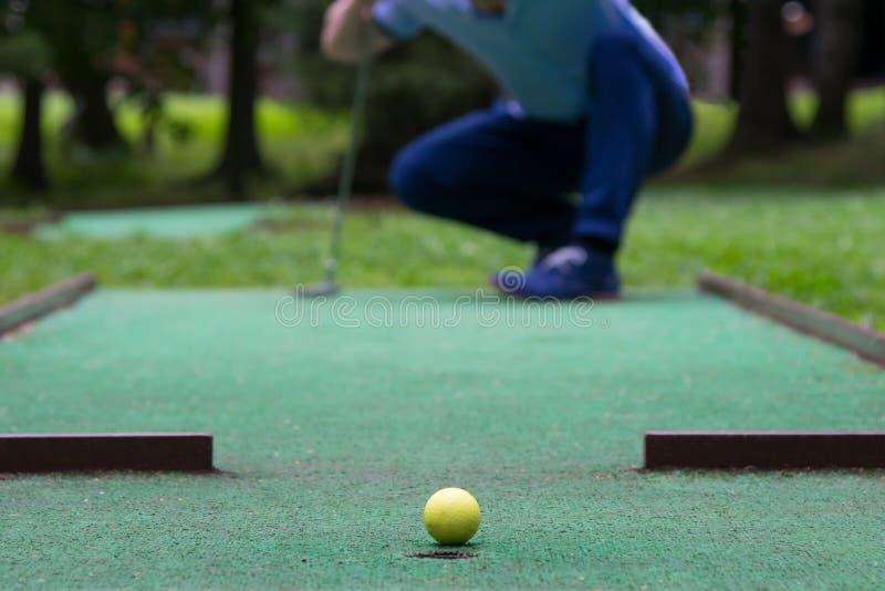 Boule jaune sur la pelouse verte, devant le mini entonnoir de golf images libres de droits
