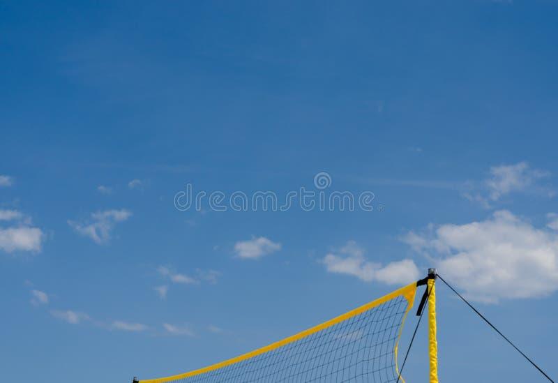 Boule nette jaune de volée de plage de filet contre le ciel bleu photographie stock