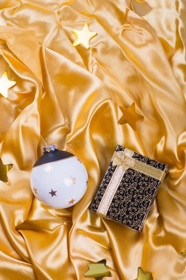 Boule noire et blanche élégante de Noël avec les étoiles et le boîte-cadeau sur le tissu d'or de satin photographie stock libre de droits
