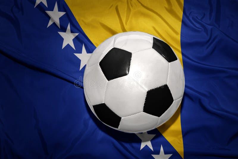 Boule noire et blanche du football sur le drapeau national de la Bosnie-Herzégovine photos libres de droits