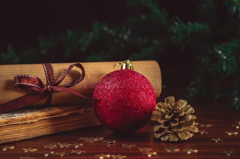 Boule rouge de Noël avec une lettre de cône et de rouleau sur le vieux livre sur la fin en bois de table  photos stock
