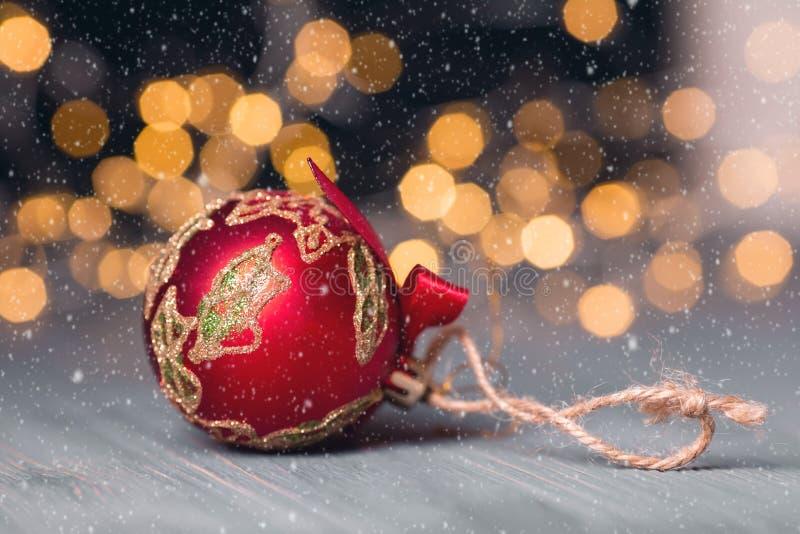 Boule rouge de Noël sur le fond abstrait clair cardez la salutation de Noël Effets de neige Orientation molle photos libres de droits