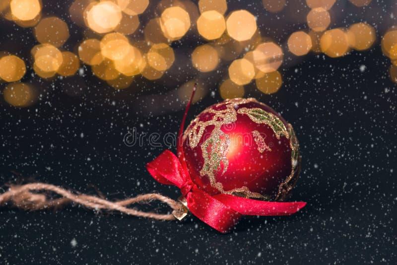 Boule rouge de Noël sur le fond abstrait clair cardez la salutation de Noël Effets de neige Orientation molle image libre de droits