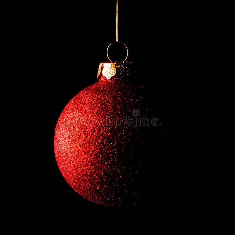 Boule rouge de Noël sur le fond noir Carte de voeux photographie stock libre de droits