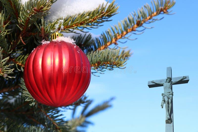 Boule rouge de Noël sur le vrai arbre de Noël extérieur vivant avec le crucifix semi-transparent image stock