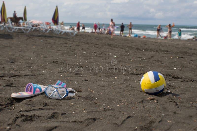 Boule, sandale colorée et verres de natation sur la plage Photo brouillée des personnes sur la plage de sable Voyage ou concept d image stock