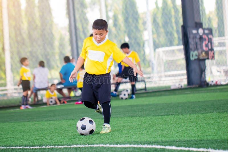 Boule trouble avec la course asiatique de vitesse de footballeur d'enfant pour tirer la boule au but sur le gazon artificiel image libre de droits