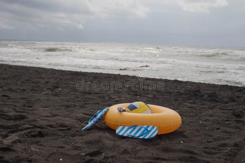 Boule, verres de natation, sandale, et anneau de flottement sur la plage Pendant les vacances d'été image libre de droits