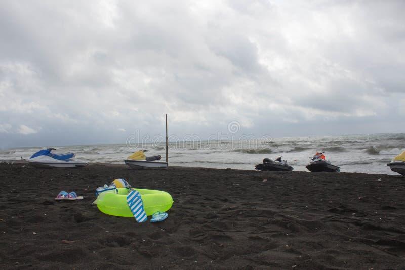 Boule, verres de natation, sandale, scooter de l'eau et anneau de flottement sur la plage croisement, montée subite photographie stock