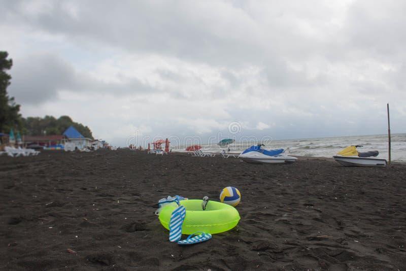 Boule, verres de natation, sandale, scooter de l'eau et anneau de flottement sur la plage Les personnes brouillées sur le sable é photo stock