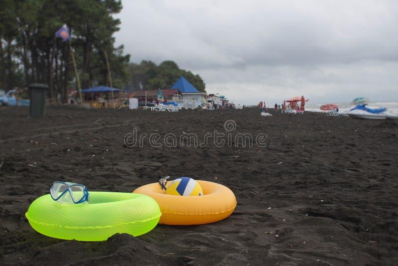 Boule, verres de natation, scooter de l'eau et anneau deux de flottement sur la plage Personnes brouillées sur la plage de sable  photographie stock libre de droits