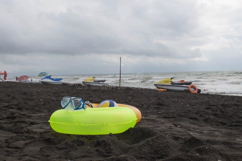 Boule, verres de natation, scooter de l'eau et anneau deux de flottement sur la plage Personnes brouillées sur la plage de sable  photo libre de droits
