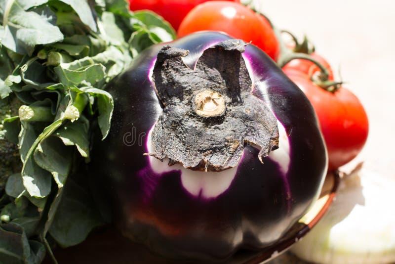 Boule violette d'aubergine avec le brocoli et les tomates rouges, healt frais image stock