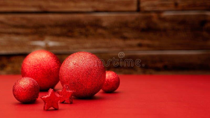 Boules éclatantes et étoiles rouges d'arbre de Noël de conception se trouvant sur une table rouge images stock