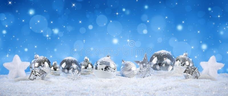 Boules argentées sur la neige avec des chutes de neige photo stock