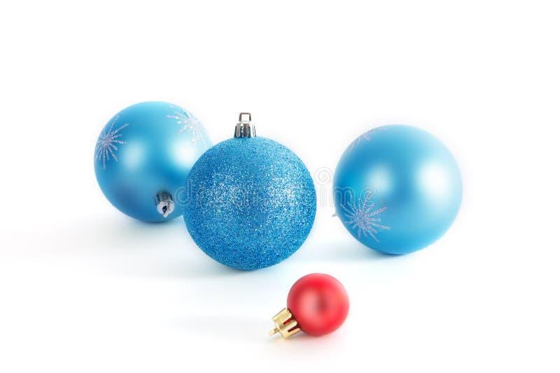Boules bleues décoratives de Noël de Noël trois et une boule rouge de Noël sur le fond blanc images libres de droits