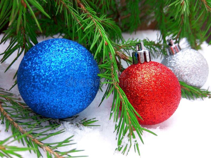 Boules bleues, rouges et argentées de nouvelle année avec l'arbre de sapin vert sur le fond neigeux images libres de droits