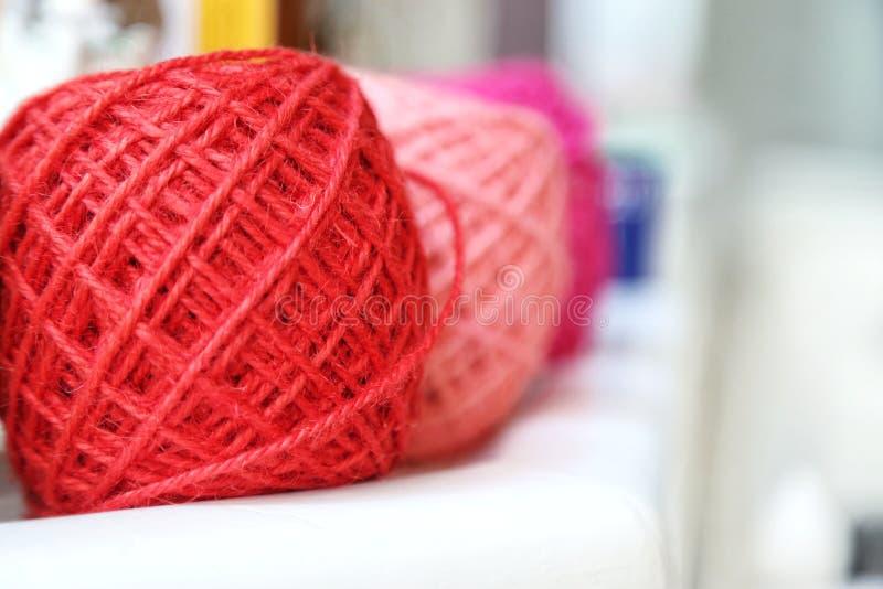 Boules colorées et aiguilles de fil à tricoter sur la table blanche sur le fond brouillé Fermez-vous des boules de laine colorées image libre de droits
