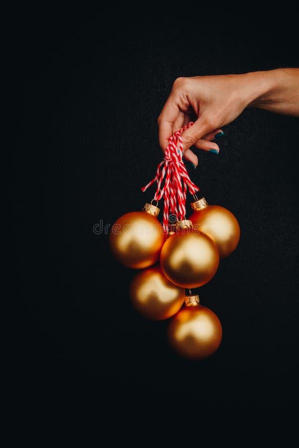 Boules d'or de Noël chez la main de la femme d'isolement sur le fond noir Invitation d'an neuf photos libres de droits
