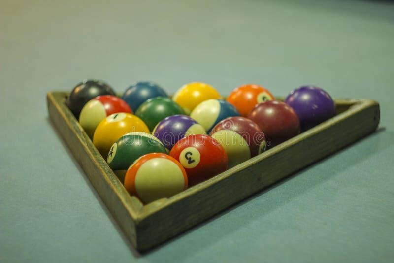 Boules de billard multicolores brouillées sur une nappe bleue dans une triangle en bois nombres sur des boules de billard photographie stock libre de droits