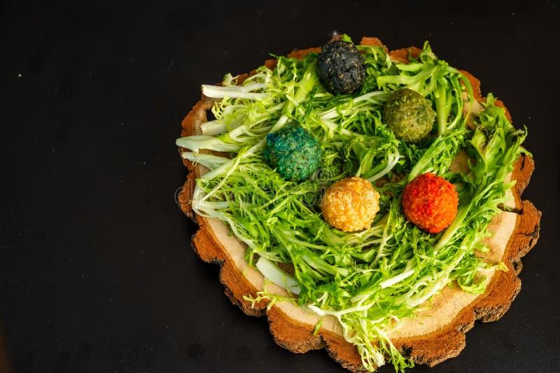 Boules de fromage d'un plat en bois avec des verts image stock