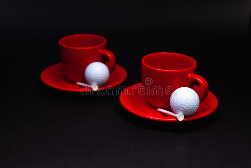 Boules de golf blanches et tasses rouges de thé sur la table noire image stock