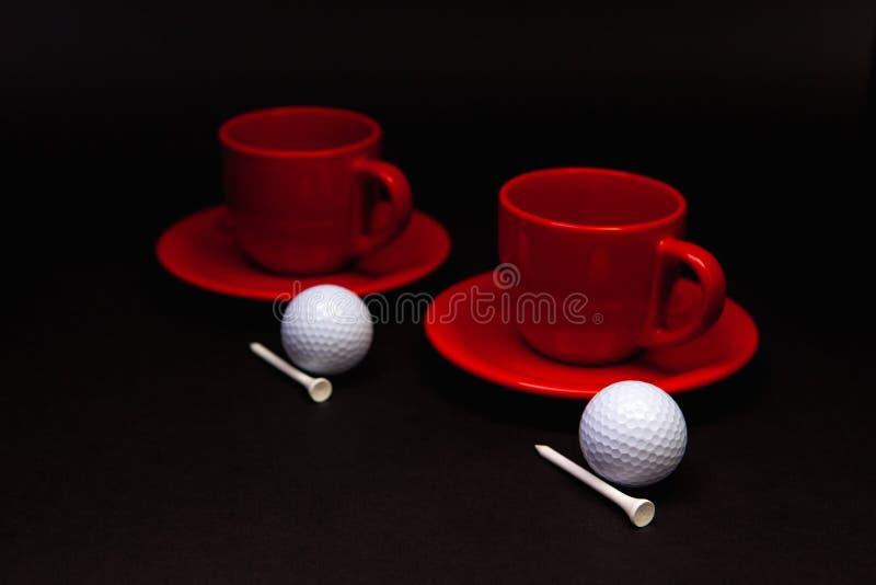 Boules de golf blanches et tasses rouges de th? sur la table noire photos libres de droits