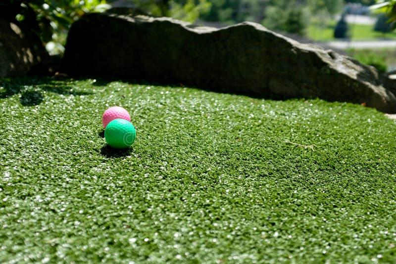 Boules de golf miniature colorées sur le putting green photos libres de droits